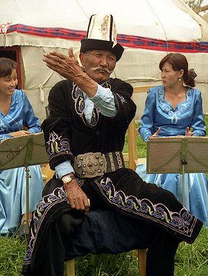 A traditional Kyrgyz manaschi performing part ...